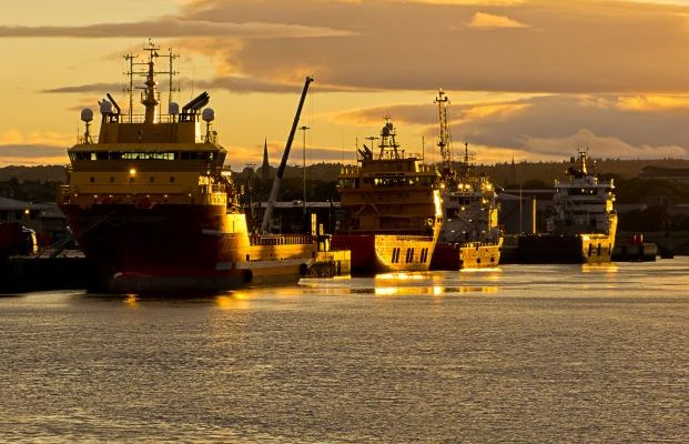 Four ships moored in Aberdeen harbour as the sun sets.